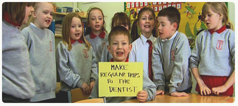 Class holding sign about going to the dentist
